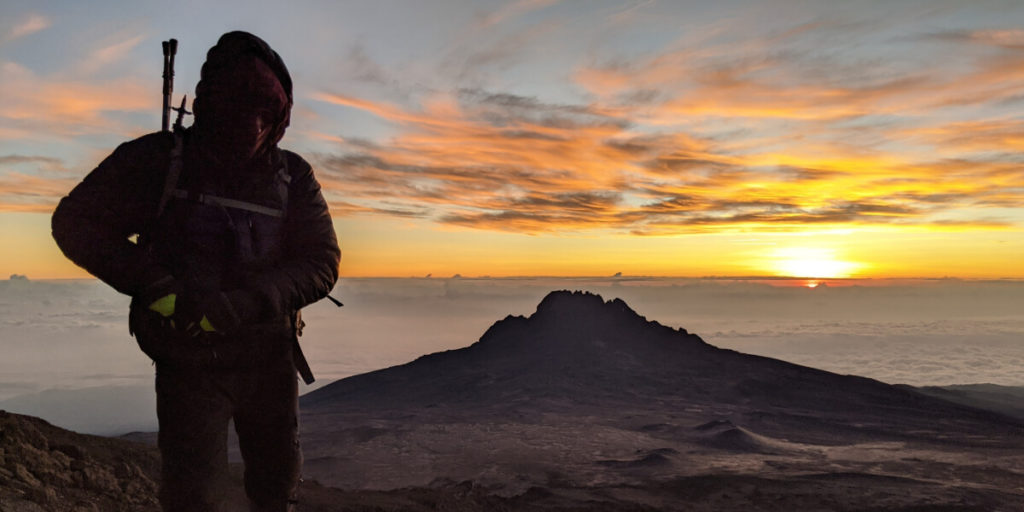 Man in black jacket with incredible Kilimanjaro summit sunset behind